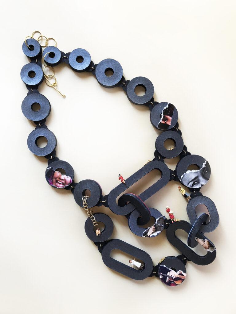 collana blu con collage e piccoli personaggi miniatura